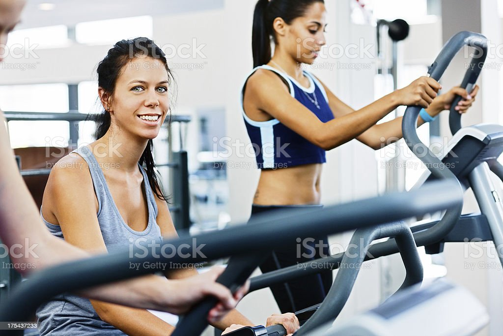 Pretty women staying fit by using gym equipment stock photo