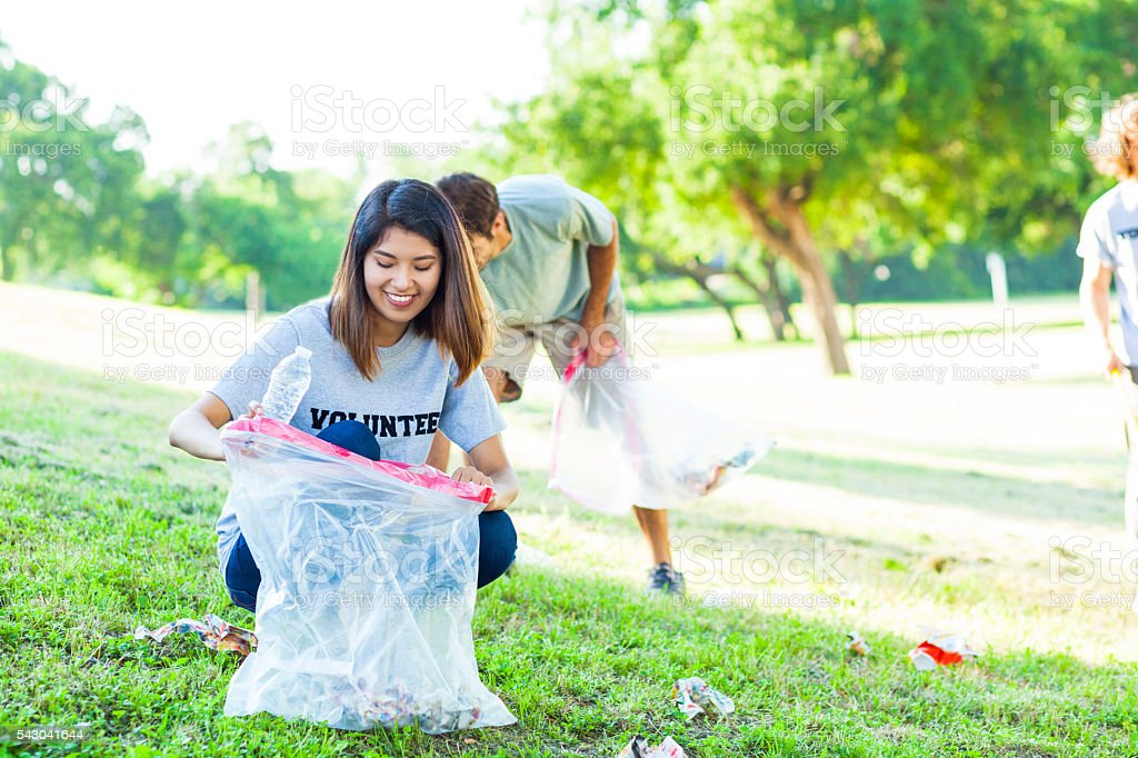 Pretty young Asian female volunteer picks up trash in park stock photo