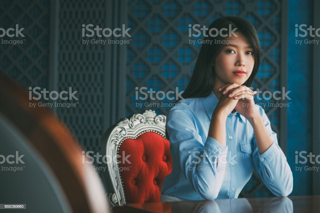 Pretty Young Asian Woman with Hands under Chin stock photo