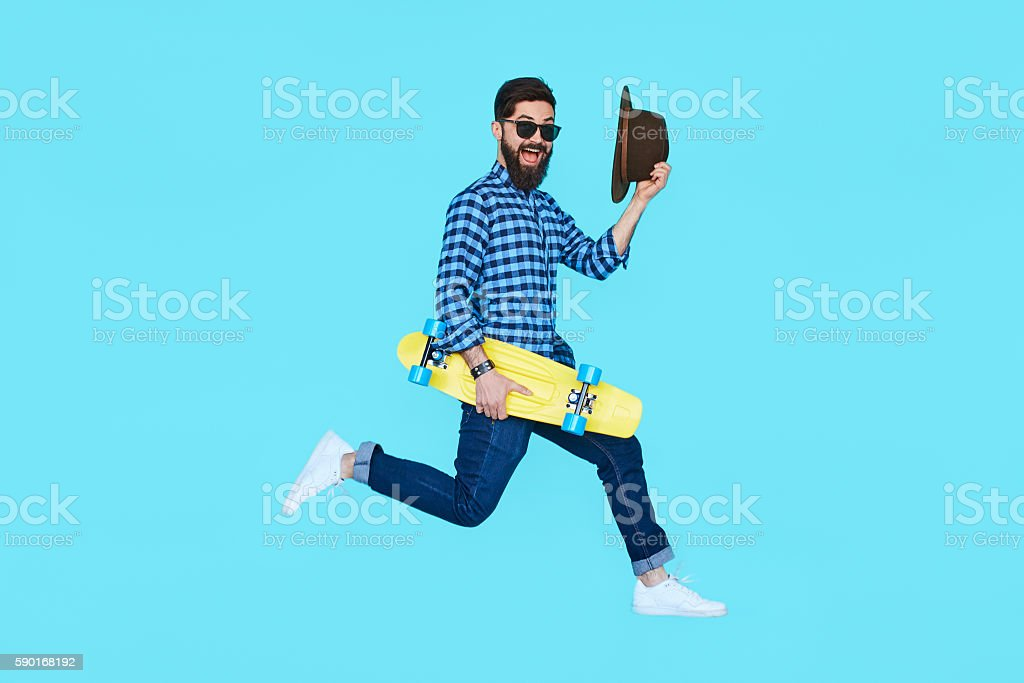 Pretty young bearded man jumping with yellow skateboard stock photo