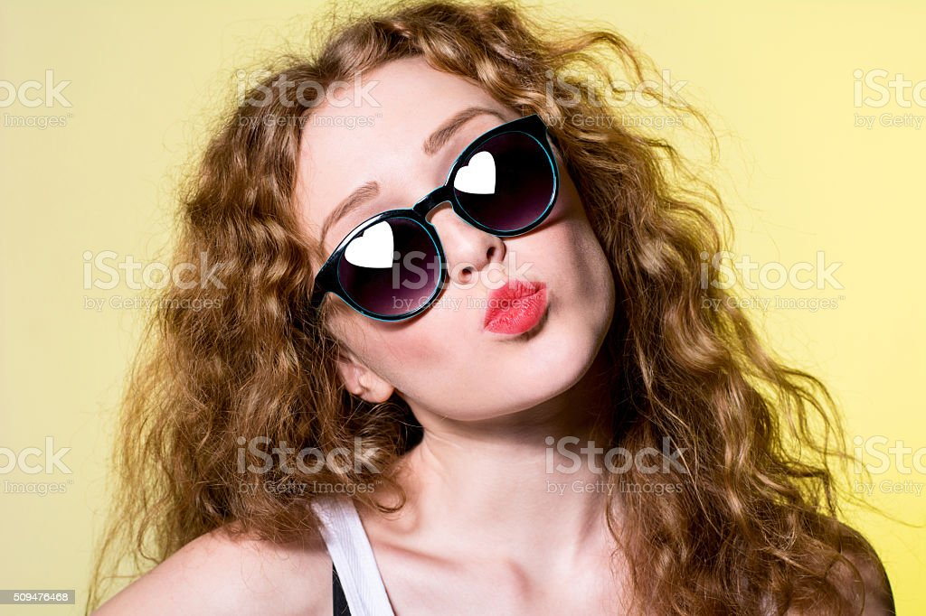 Pretty young beautiful girl in sunglasses makes lips kiss stock photo