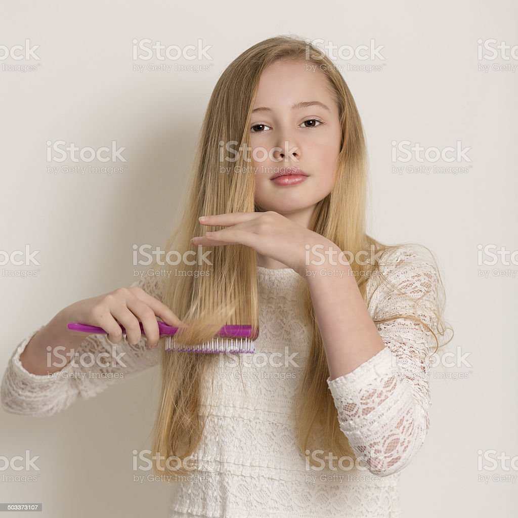 Pretty Young Blond Girl Brushing Her Hair stock photo
