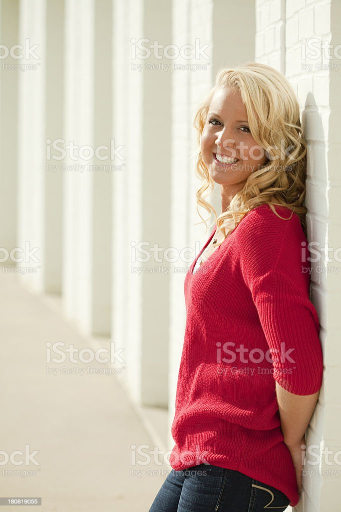 Pretty Young Blonde Girl Leaning against White Wall royalty-free stock photo