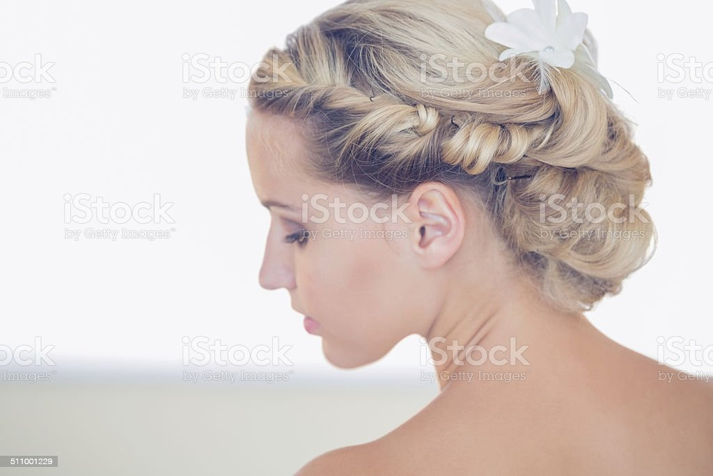 Pretty young bride looking down stock photo