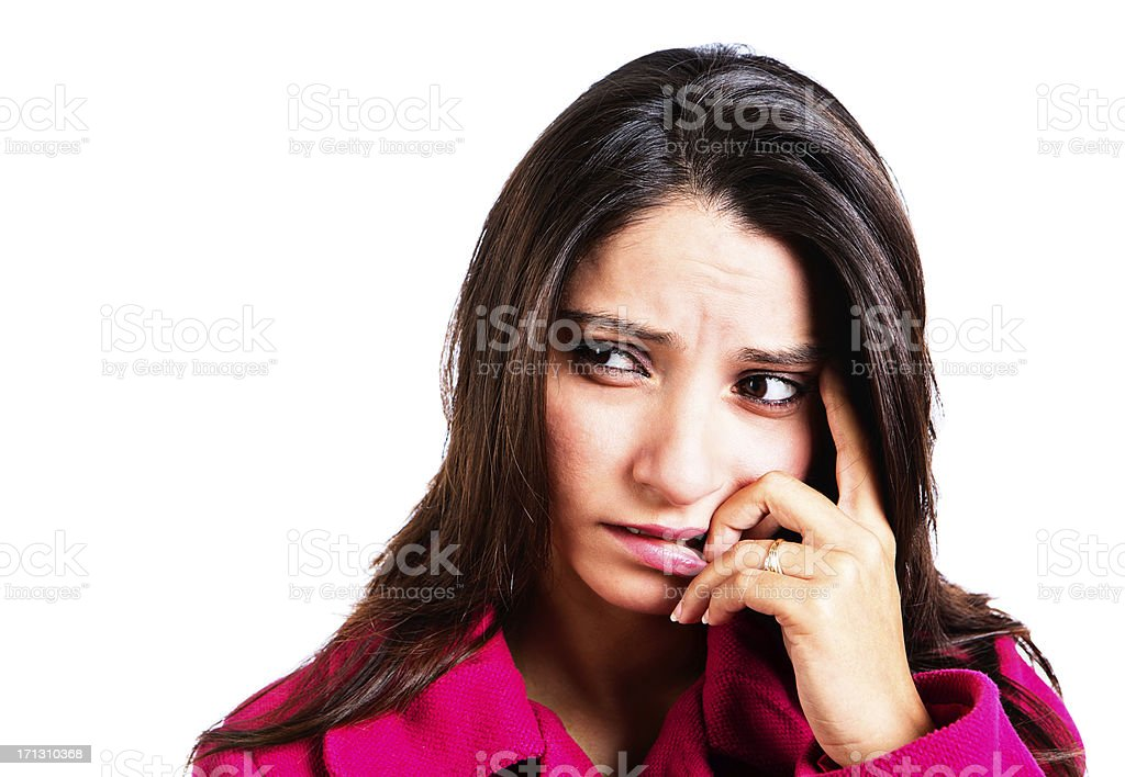 Pretty young brunette bites nails, looking nervous and worried royalty-free stock photo