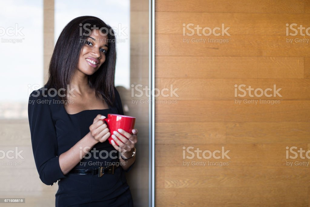 Pretty, young business lady in black strong suite hold red cup stock photo