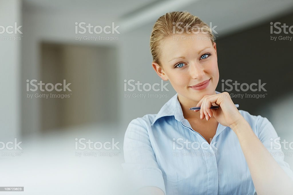 Pretty young business woman holding a pen royalty-free stock photo