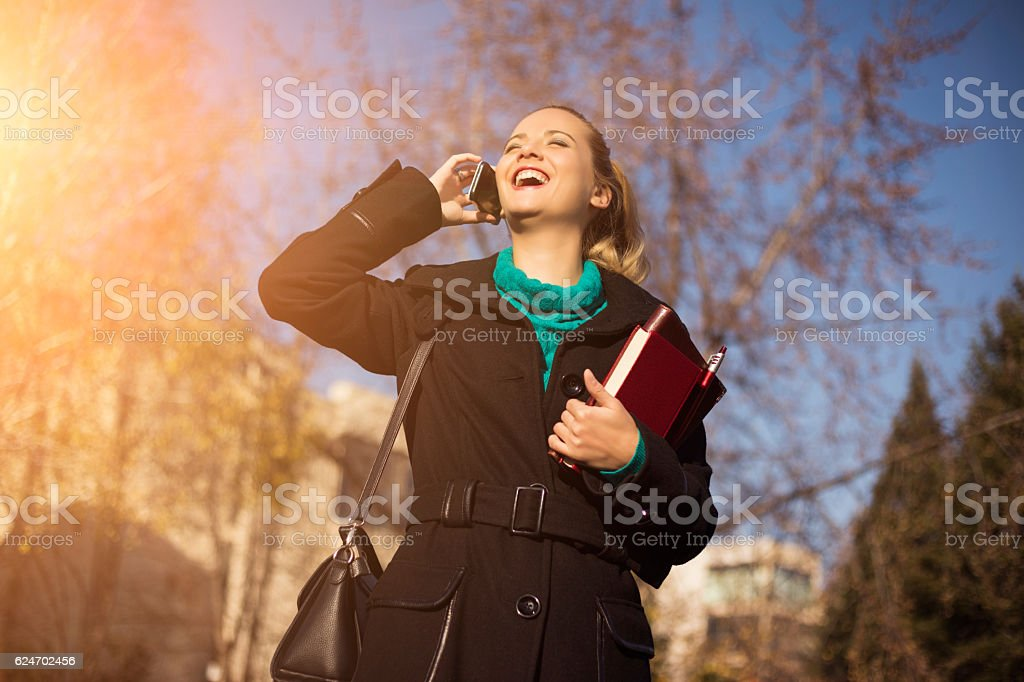 Pretty young businesswoman in the city talking on the phone. stock photo