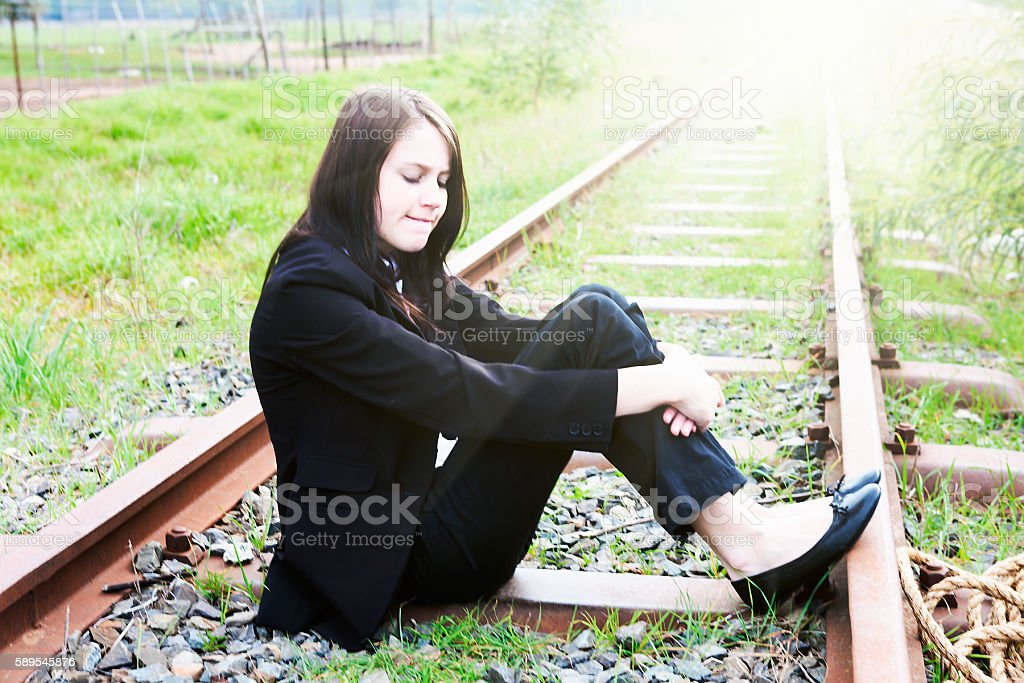 Pretty young businesswoman sitting on railway tracks looks sad stock photo