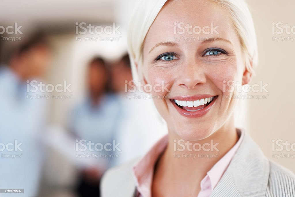 Pretty young businesswoman smiling at office stock photo