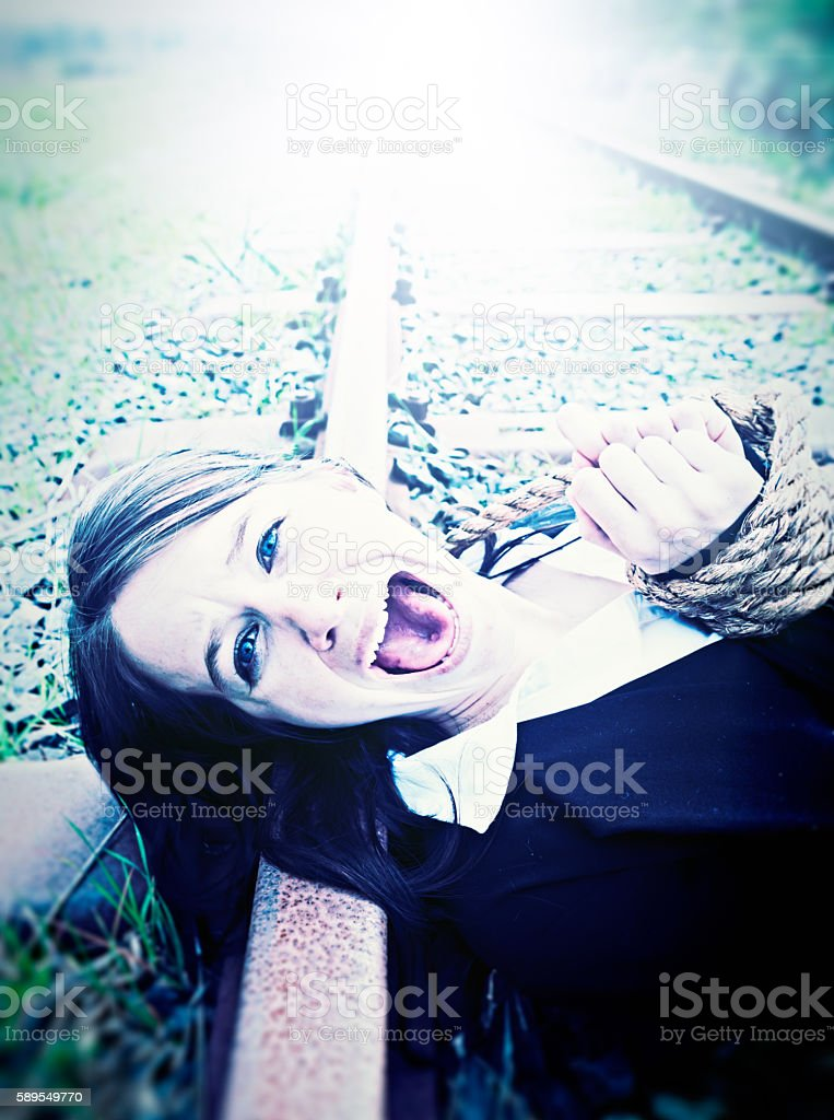 Pretty young businesswoman tied to railroad track screams for help stock photo