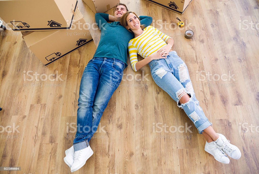 Pretty young couple moving in new home. stock photo