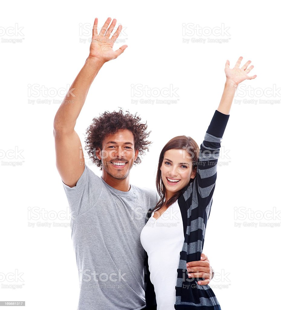 A pretty young couple with hands raised over white background stock photo