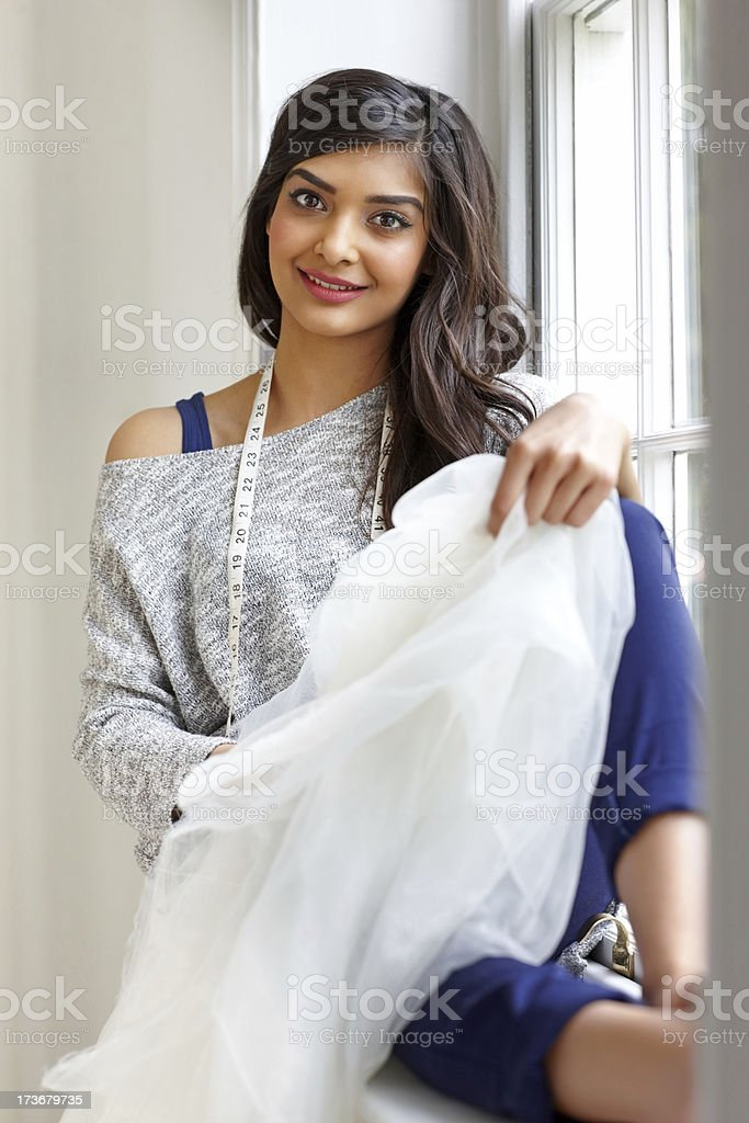 Pretty young fashion designer sitting on a window sill royalty-free stock photo