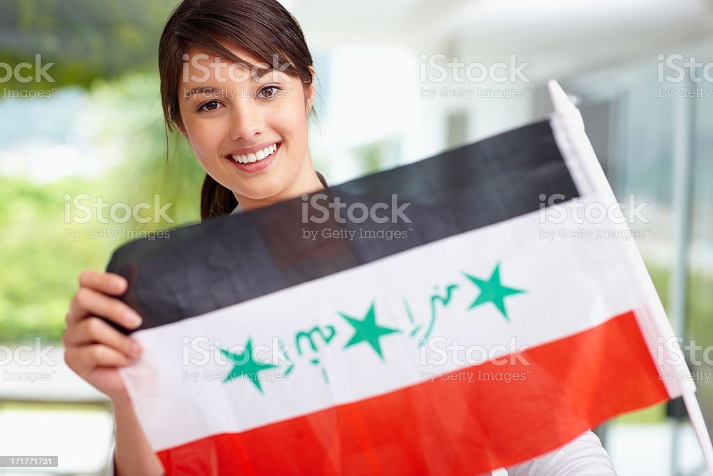 Pretty young female displaying an Iraqi flag stock photo