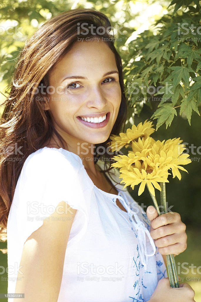 Pretty young female holding yellow flowers in a park royalty-free stock photo