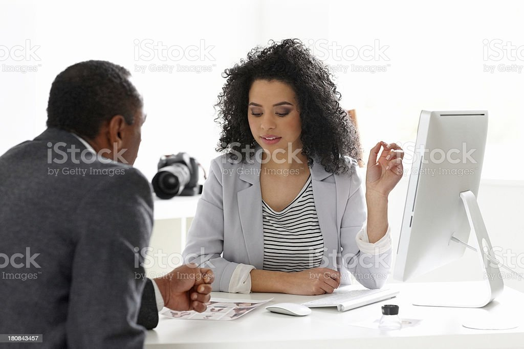 Pretty young female photo editor in discussion with her mentor royalty-free stock photo