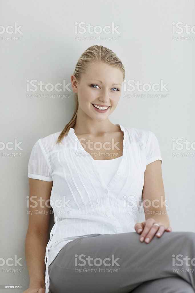Pretty young female sitting against a wall with smile royalty-free stock photo