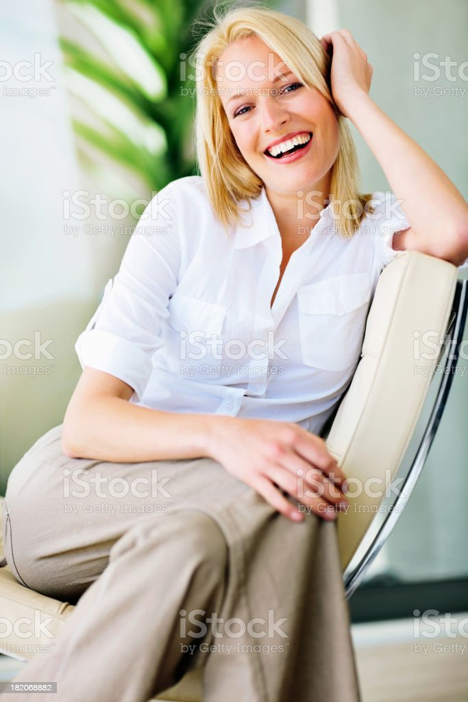 Pretty young female sitting on a chair and smiling royalty-free stock photo