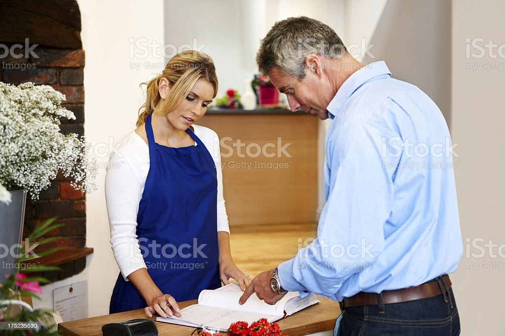 Pretty young florist attending store client royalty-free stock photo