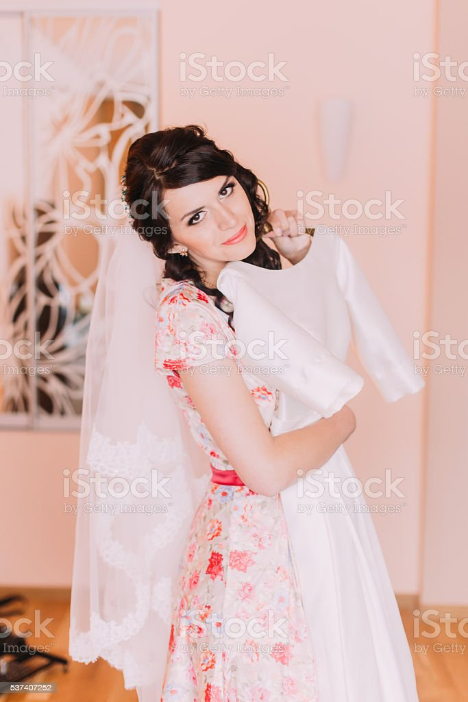 Pretty young girl holding silk wedding gown in dressing room stock photo