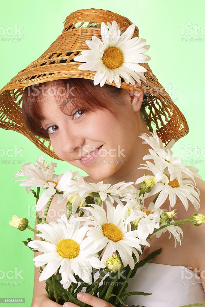 Pretty young girl in the hat with chamomile flowers royalty-free stock photo