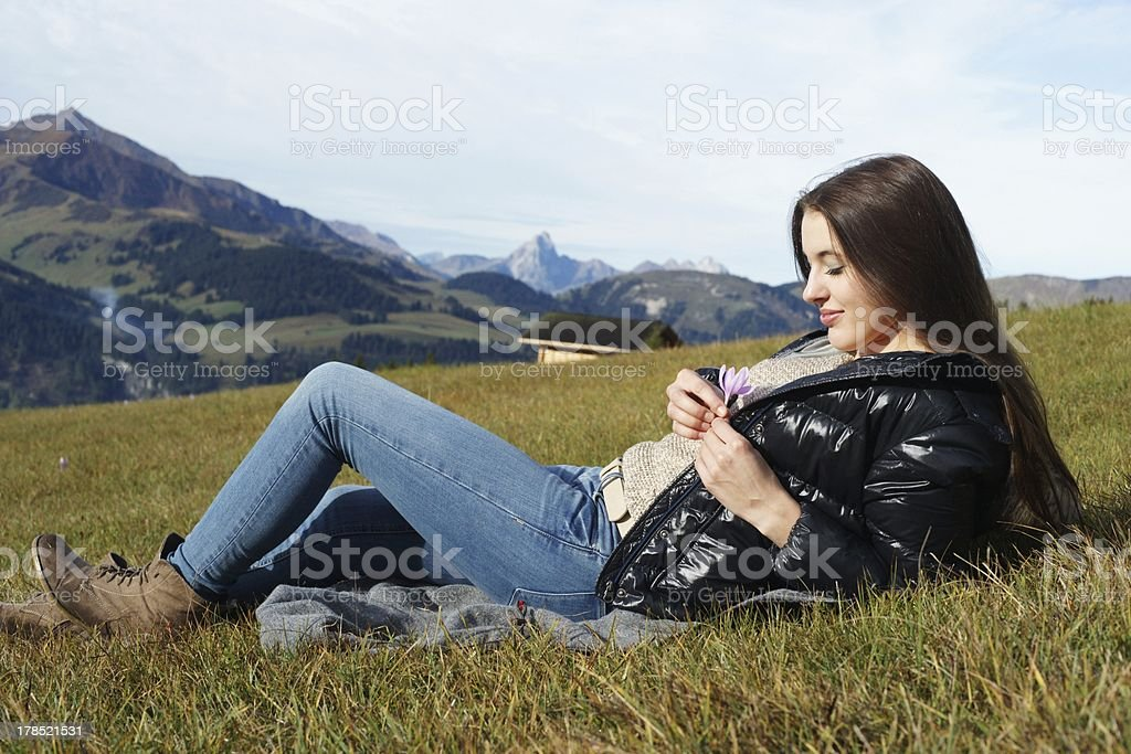 Pretty young girl in the mountains with flower royalty-free stock photo