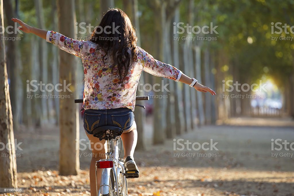 Pretty young girl riding bike in a forest. stock photo