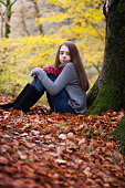 Pretty young girl sitting on dried leaves in a forrest