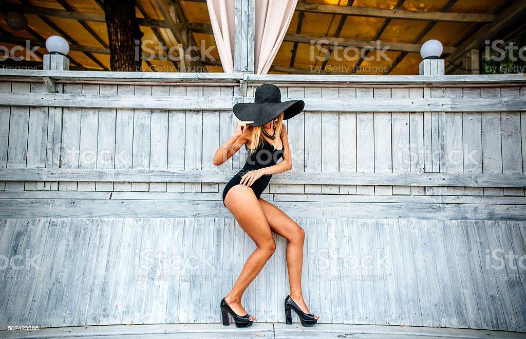Pretty young girl standing near wooden wall in black swimwear stock photo