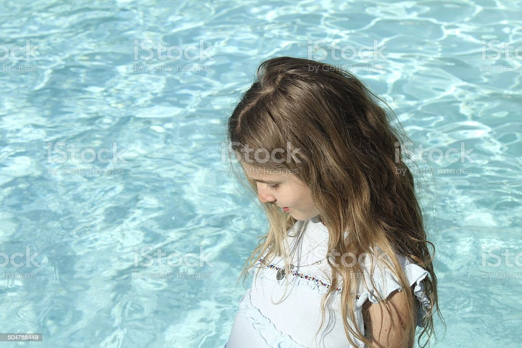 Pretty young girl with blond hair near a pool royalty-free stock photo