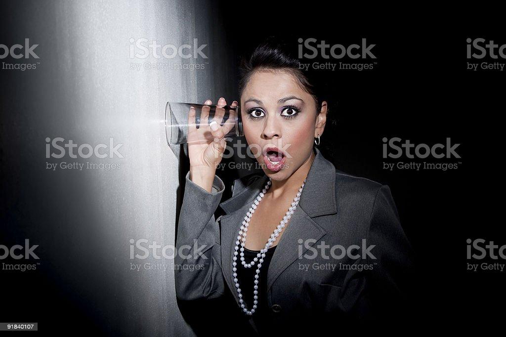 Pretty young Hispanic woman using glass to eavesdrop stock photo
