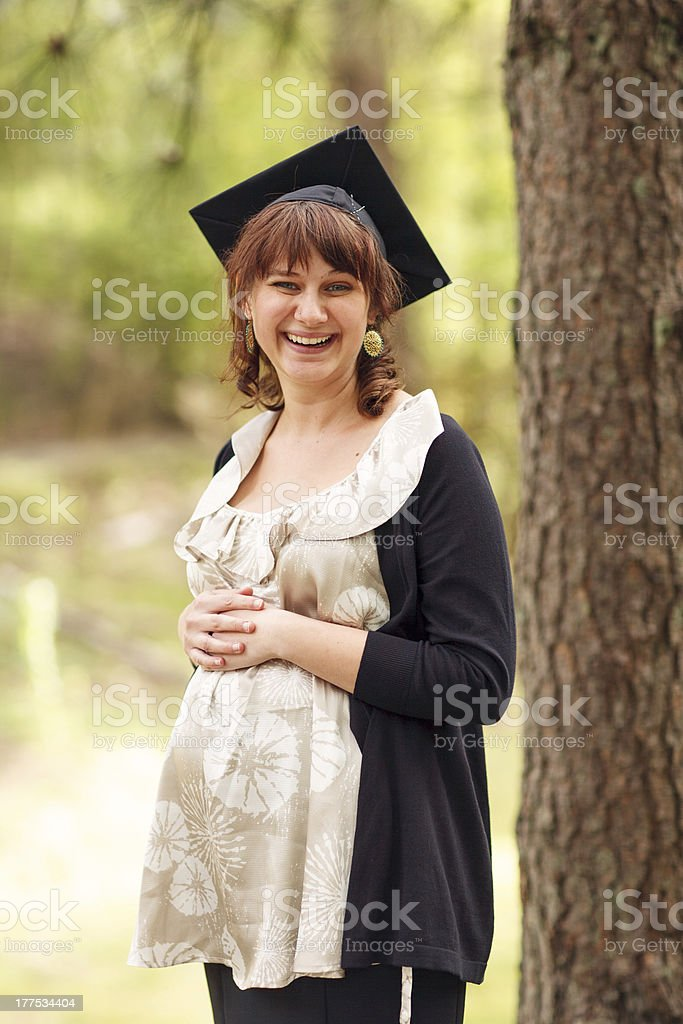 Pretty Young Pregnant College Graduate Smiling in Cap and Gown royalty-free stock photo