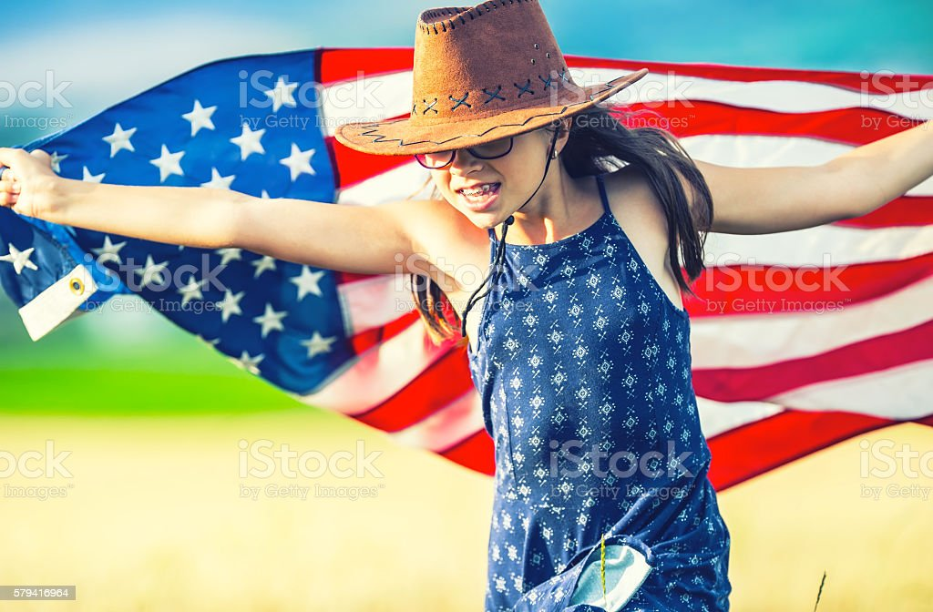 Pretty young pre-teen girl with cowboy hat and American flag. stock photo
