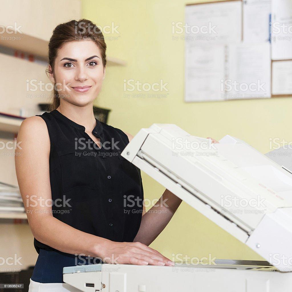 Pretty young secretary using a copy machine stock photo