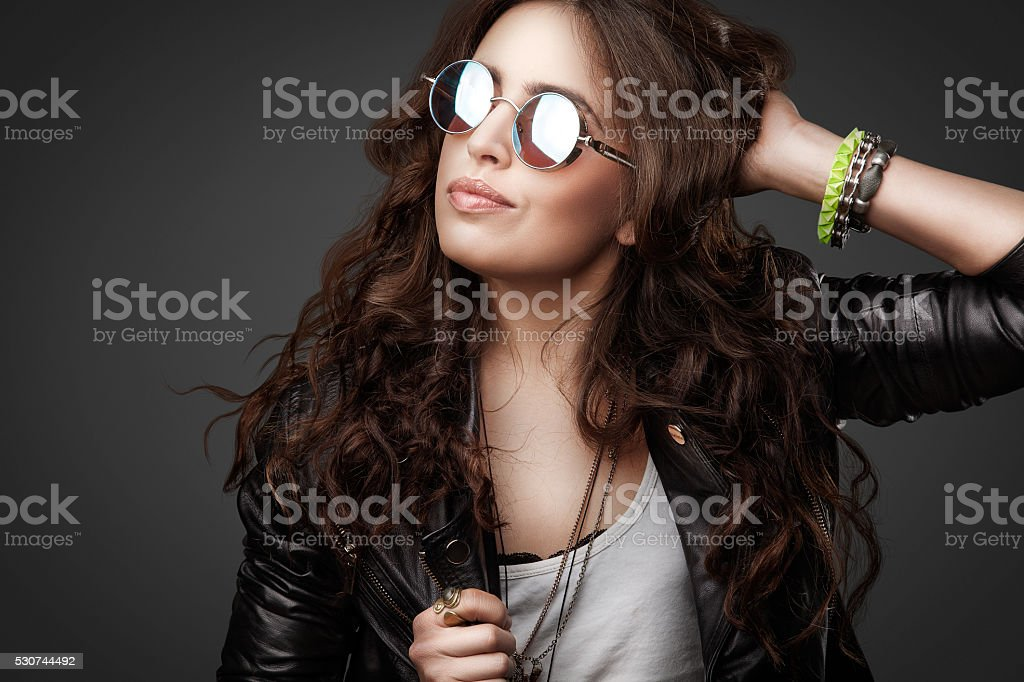 Pretty young stylish girl in leather jacket and round sunglasses stock photo