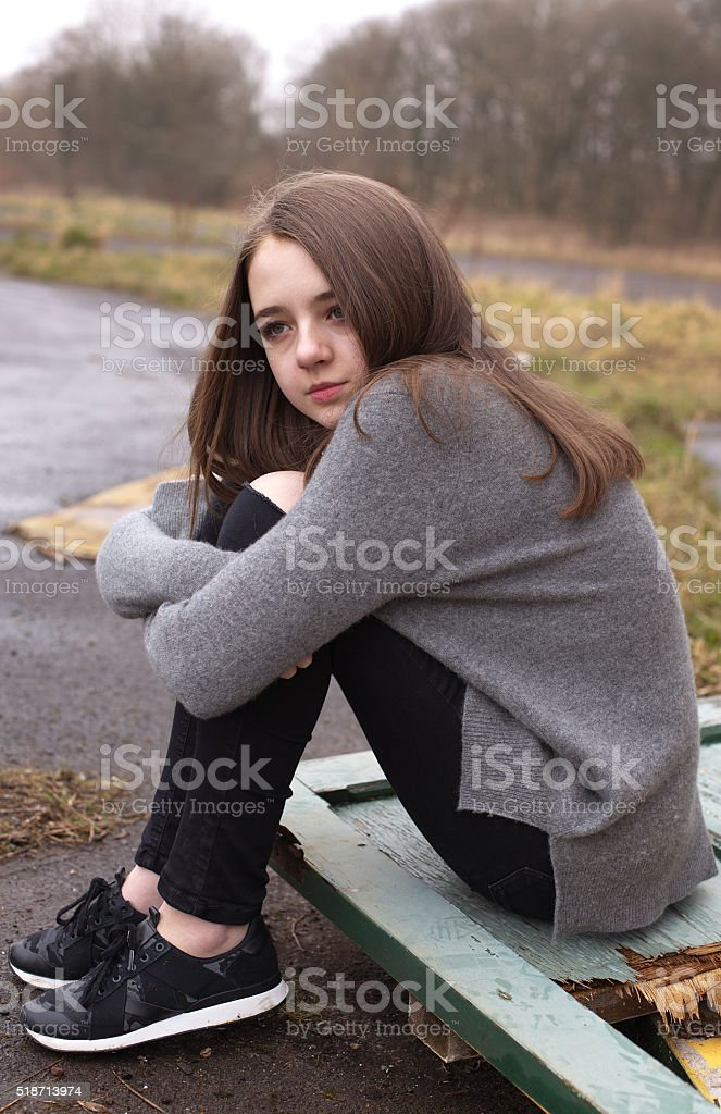 Pretty young teenage girl sitting outside on a damp day stock photo