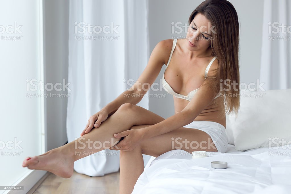 Pretty young woman applying body cream on legs. stock photo