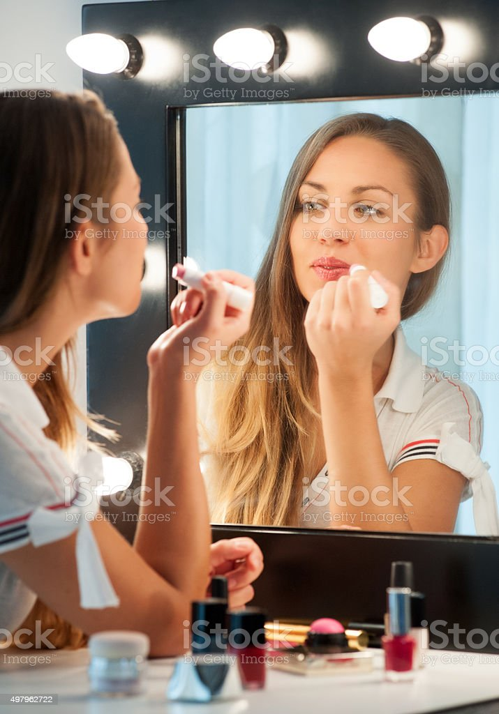 Pretty young woman applying lipstick stock photo