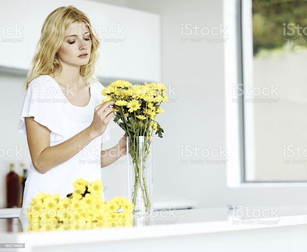 Pretty young woman arranging flowers in vase at home royalty-free stock photo