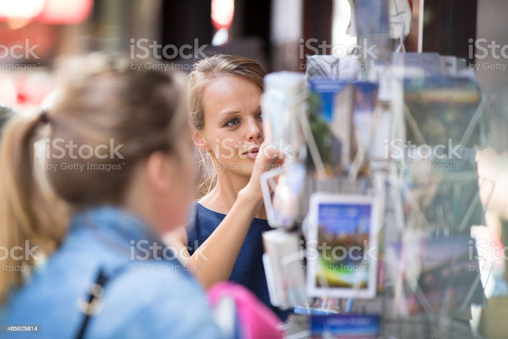 Pretty, young woman buying a postcard stock photo