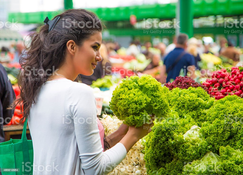Pretty young woman buying vegetables on the market stock photo