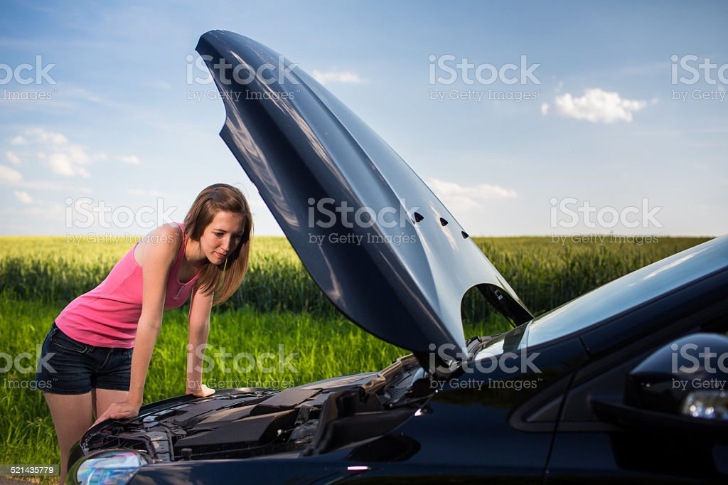 Pretty, young woman calling the roadside service stock photo