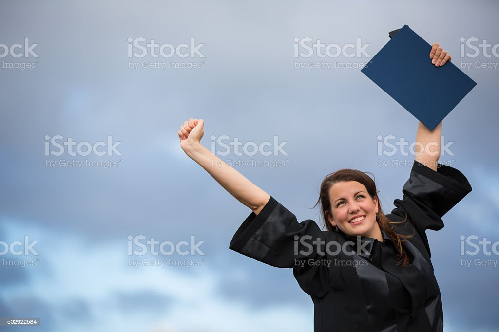 Pretty, young woman celebrating joyfully her graduation stock photo
