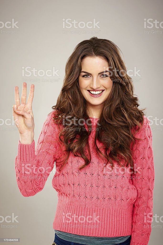 Pretty young woman counting with three fingers royalty-free stock photo