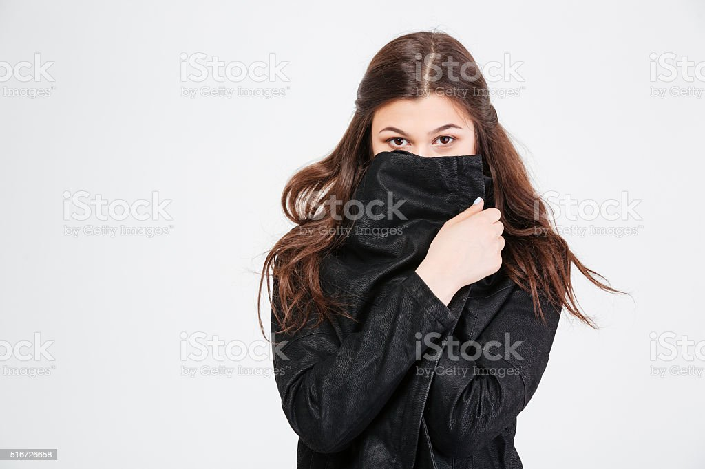 Pretty young woman covered her face with black jacket stock photo