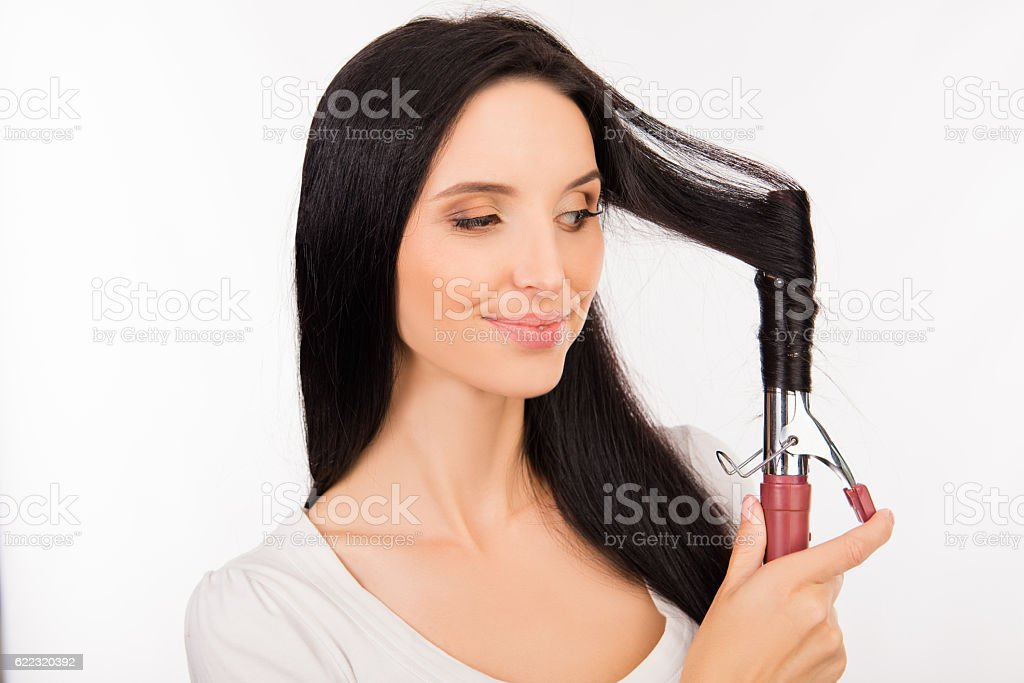Pretty young woman curling her hair stock photo