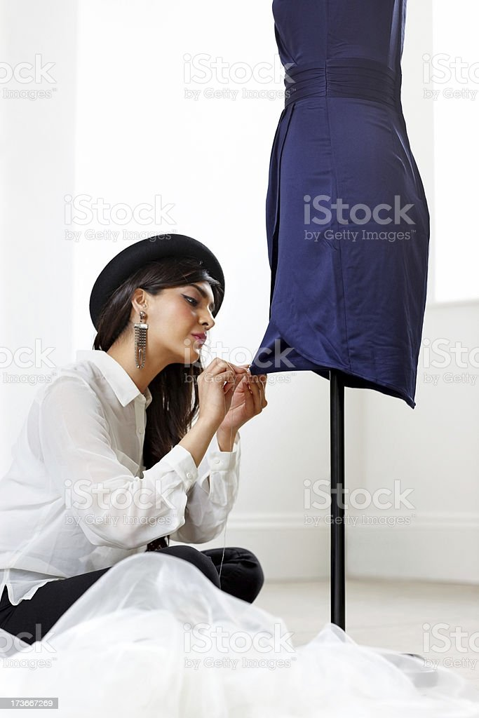 Pretty young woman designer working on mannequin royalty-free stock photo