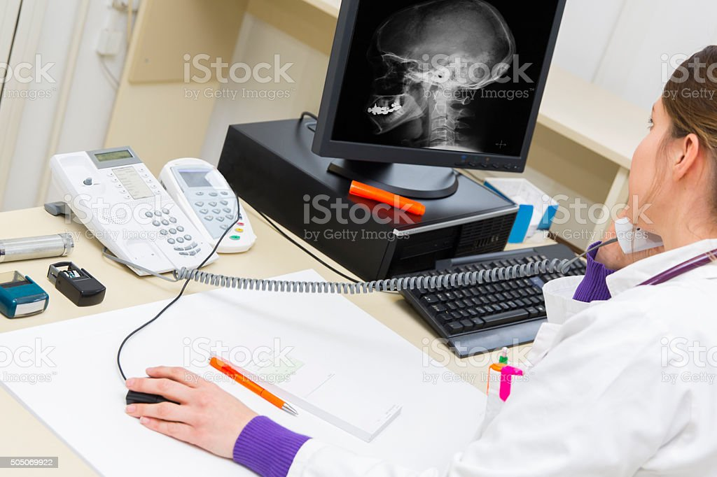 Pretty young woman doctor working,talking on phone stock photo