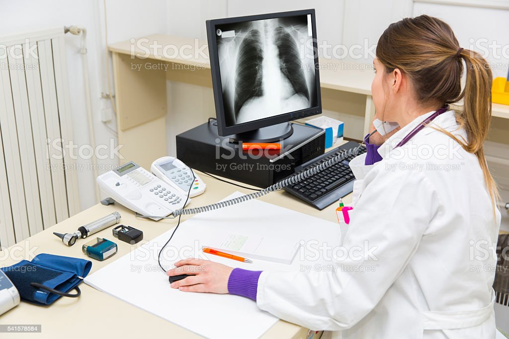 Pretty young woman doctor working,watching picture of chest X-ray stock photo